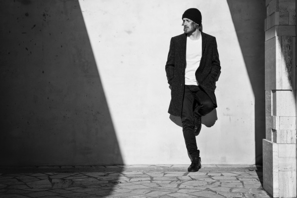 Premium photographer example: Young man leaning against a wall in black and white