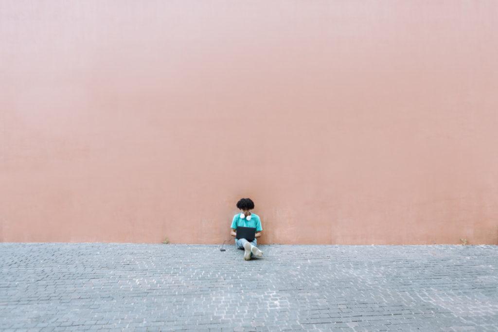 Mann Laptop Sitzen Fußweg Wand lizenzfrei royalty free foto minimalismus